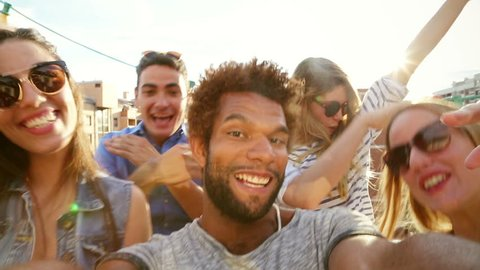 Close up of happy crazy multi-ethnic group of friends filming themselves at rooftop party on sunny day, graded