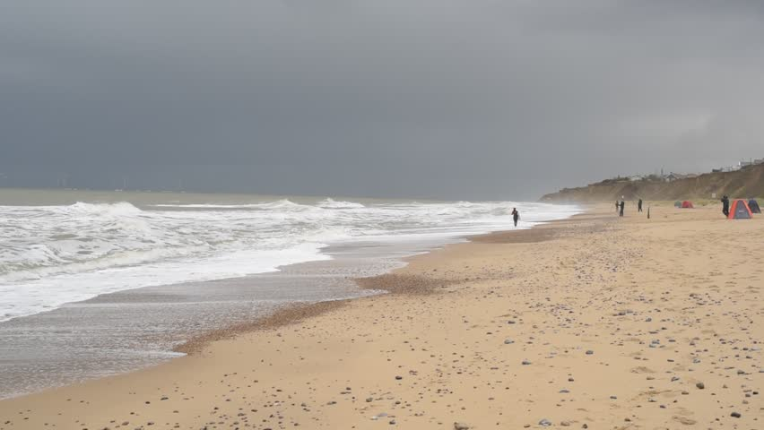 People enjoy the beach on a windy cloudy day in the UK Norfolk coast