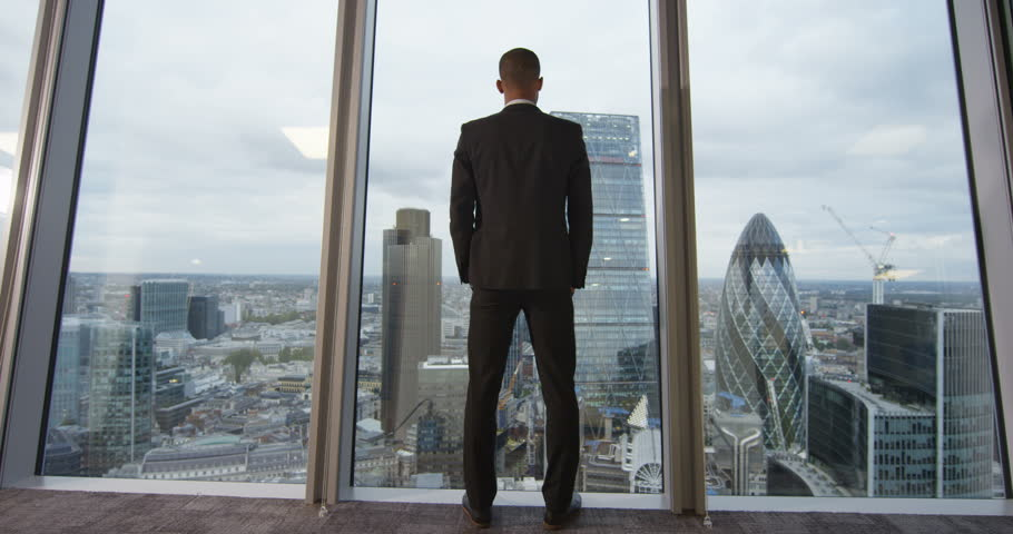 4K View from behind of young successful business executive looking out at view of the city. View from the window shows famous London skyline with iconic buildings. Slow motion. #21223897