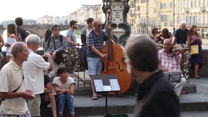 "Florence, October 2016: Tourists and street artist musicians on old bridge "" Ponte Vecchio "" over the Arno River, a popular tourist destination of Europe , on October 2016, Florence, Italy"