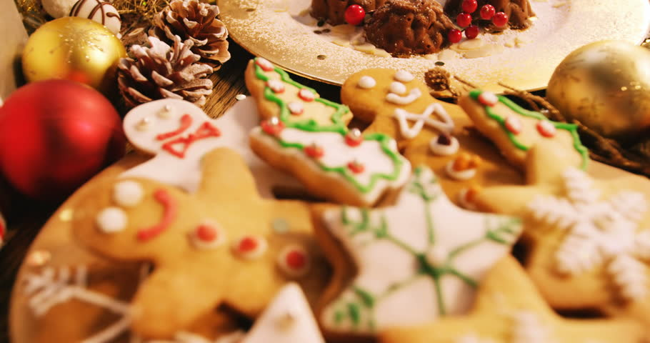 Close-up of various christmas desserts and gifts on wooden table 4k #21266539