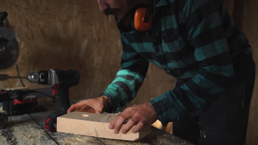of carpenter's hands using drill on wooden plank
