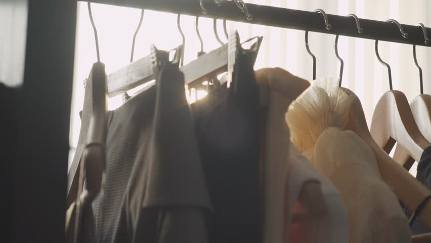 Close-up: a hanger for clothing. Designer clothing collection. Designer with a ready collection. Sunlight between hangers for clothes. Solar Design Studio. Atelier, bathed in natural sunlight.