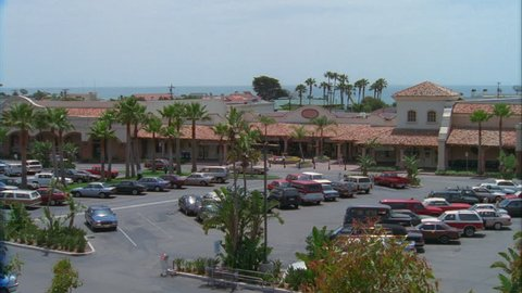 day Wide High Down Push stucco strip mall shopping centeRight tile roof, palm trees Ocean background