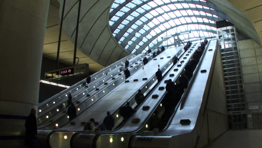 Wide shot of commuters on escalator at Canary Wharf Station, London Underground, UK