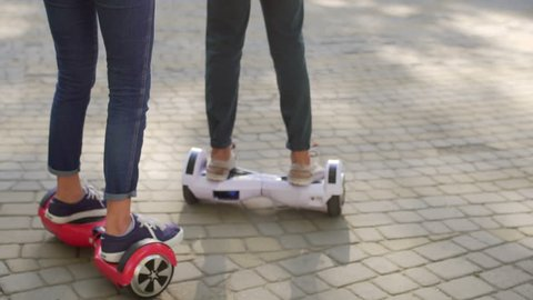 Young man and woman having fun with Hover board in the park. Content technologies. a new movement. Close Up of Dual Wheel Self Balancing Electric Skateboard Smart