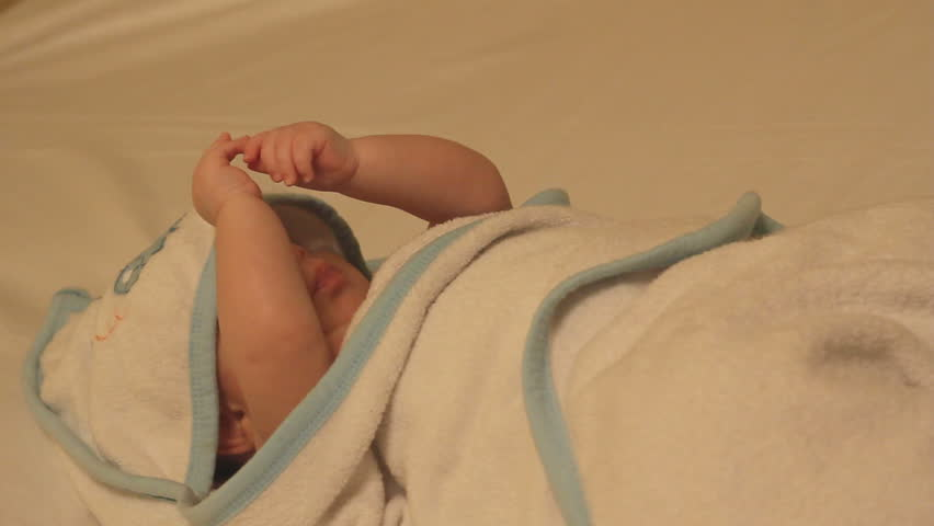 Relaxed baby in a towel after bath