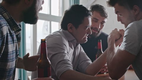 Asian man arm wrestling his friend at party while their mates cheering and laughing