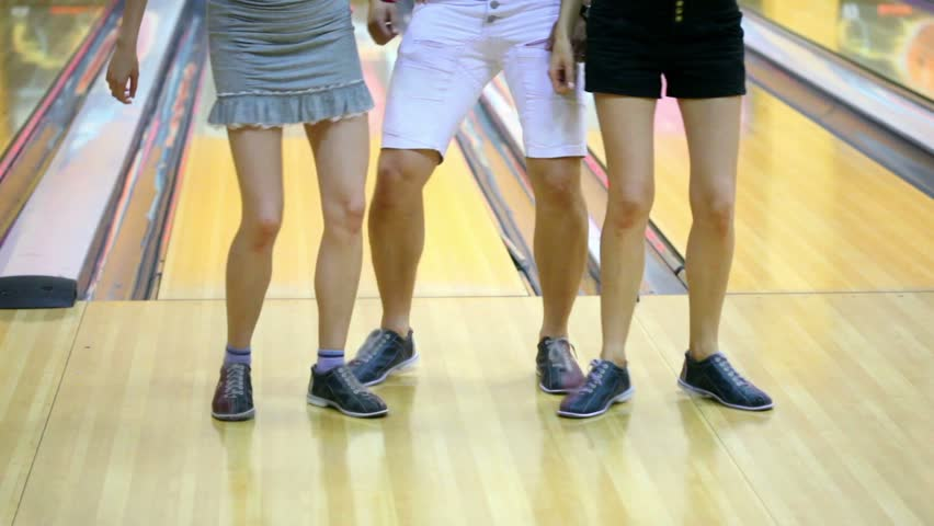 Two girls with one guy dance in bowling club, only legs are visible | Shutterstock HD Video #2135387