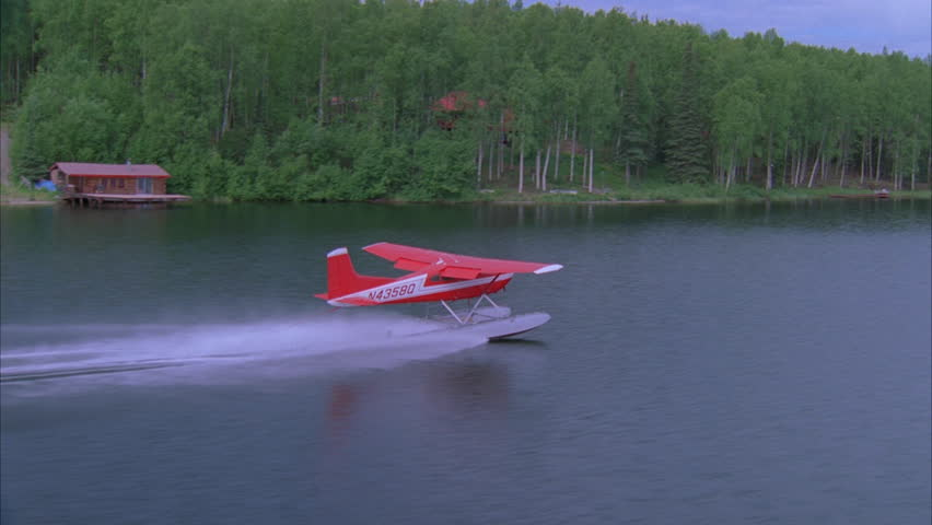 day Aerial left right with seaplane over dense green woods forests secluded 2 story homes lake Seaplane touches down lake, takes again Various angles seaplane fly's over more woods