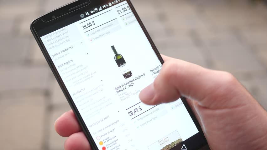 MONTREAL, CANADA - November 2016 : Shopping online wine bottles on mobile website on a smartphone.
