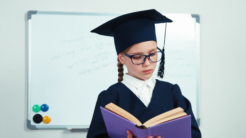 Close-up portrait happy student girl 7-8 years graduate in the mantle and hat reading her book and smiling at camera with teeth   Shutterstock HD Video #21362569