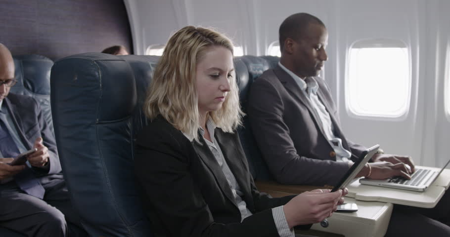 Mixed race business passengers chat while using computers in first class section of commercial airliner.  Medium shot with camera dolly and focus on female passenger.