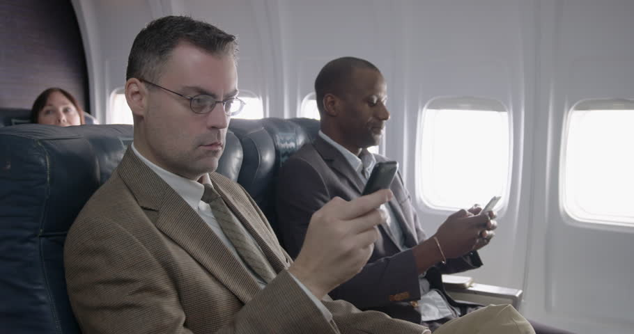 Business men using mobile phones in first class section of commercial airliner.  Medium shot with camera dolly and focus on foreground passenger | Shutterstock HD Video #21373447