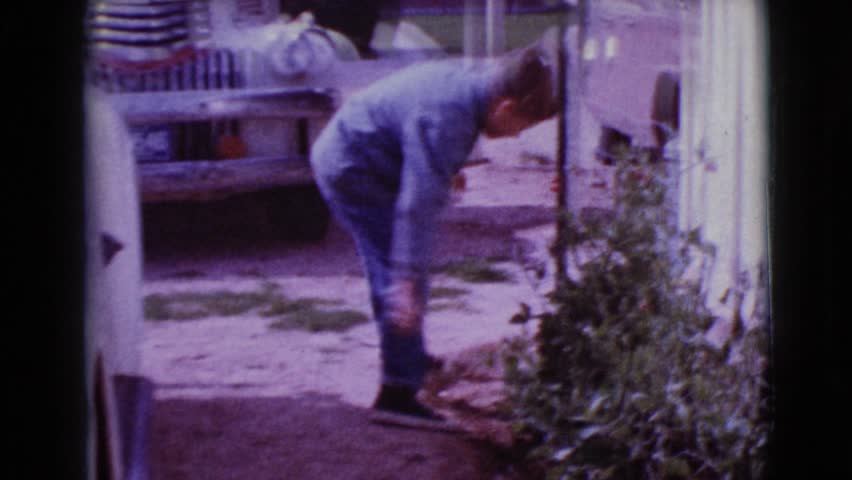 CLARKSDALE, ARIZONA 1968: a boy taking some object from the bushes and another one approaches him | Shutterstock HD Video #21374197