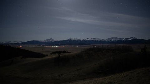 Moonset over rural traffic with snow capped mountains timelapse