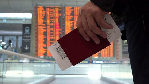 Man holding a passport in his hand going close to big timetable schedule screen, looking information in the airport about arrivals and departures terminal gate to his destination