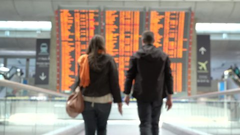Woman and man holding passports getting closer to airplane flight timetable schedule chart screen, looking for arrivals and departures to the perfect holiday destination
