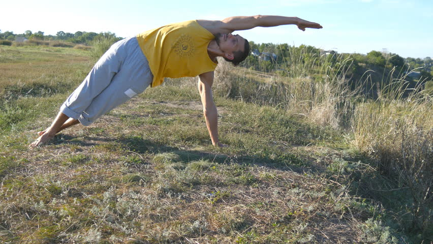 Guy practicing yoga moves and positions outdoors. Young man standing at yoga pose at nature. Athlete doing strength exercise at the hill. Landscape at background. Healthy active lifestyle. Close up | Shutterstock HD Video #21401767