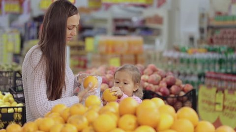 Young mother and cute baby daughter in supermarket buying fruits and vegetables