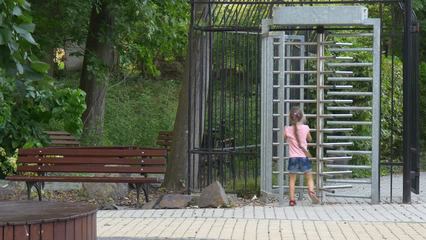 a Little Girl Waits For the Parents Near a Central Entrance Into a City Zoo. She Plays Near to a Check-Point While They Are Not Came. Many Beautiful Green Plants Grow Near to the Check-Point.
