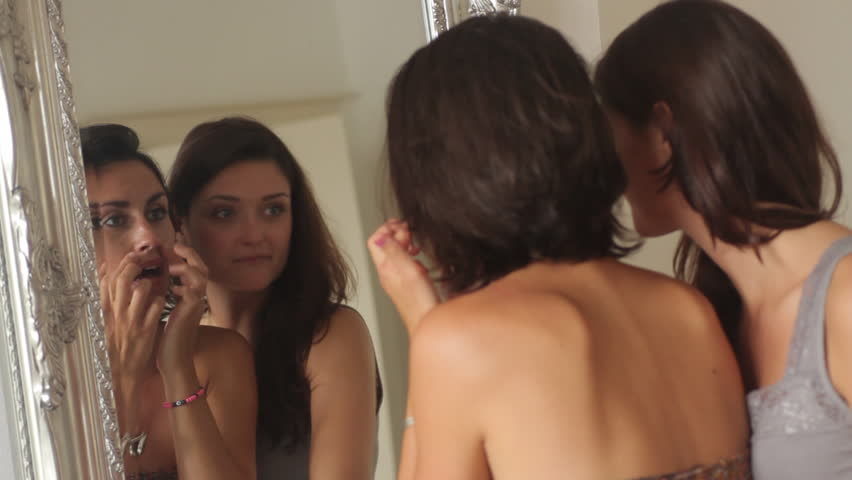 Female friends applying make up in mirror and laughing