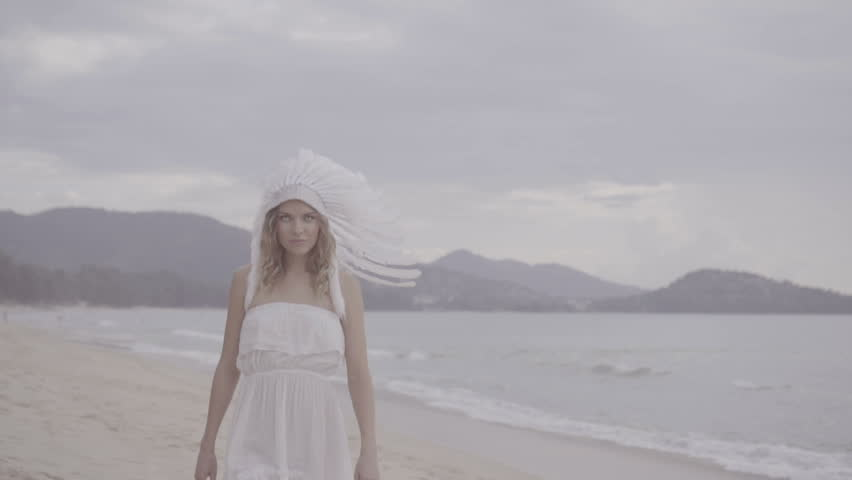 Blond woman wearing white eye lenses, dress and indian feather hat looking at the camera while walking at the beach over beautiful sea and sky background - video in slow motion | Shutterstock HD Video #21478300