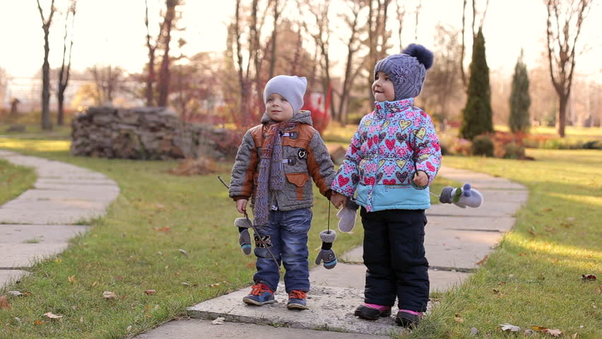 two small children walking in the park and someones call the name a child calls - Pics Of Small Children