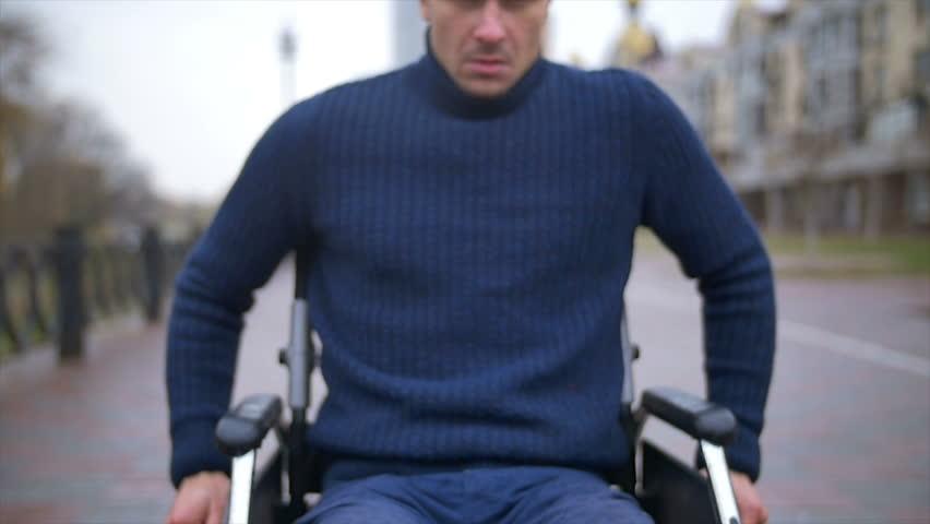 The unhappy man ride a wheelchair. Slow motion