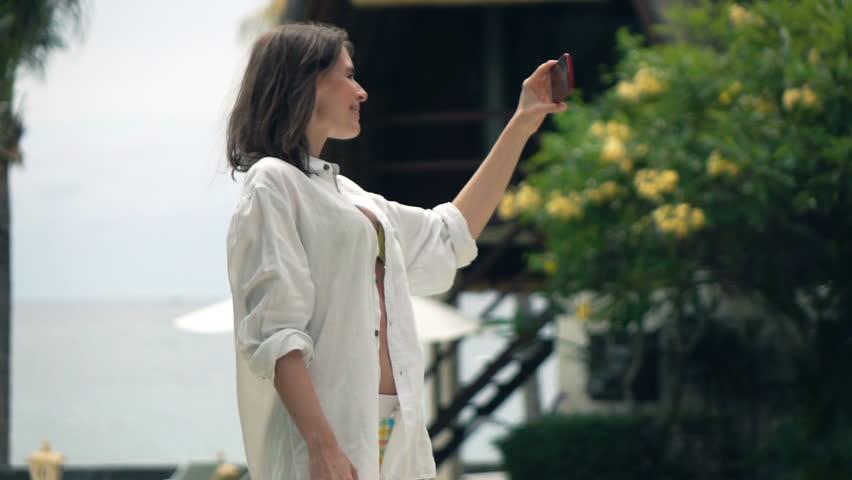 Happy woman in shirt taking selfie photo with cellphone in garden, super slow motion 240fps  | Shutterstock HD Video #21494317