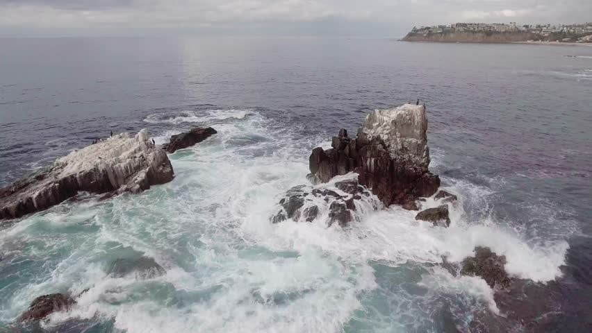 Waves crashing over rocks with birds on the rocks.  Rocks located just off shore from Crescent Bay in Laguna Beach, California.