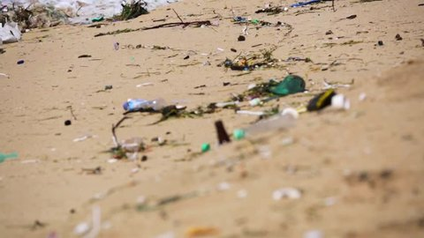 A lot of trash and plastic wastes on a beach after the storm. Ocean surf. Nusa Dua beach. Bali, Indonesia.