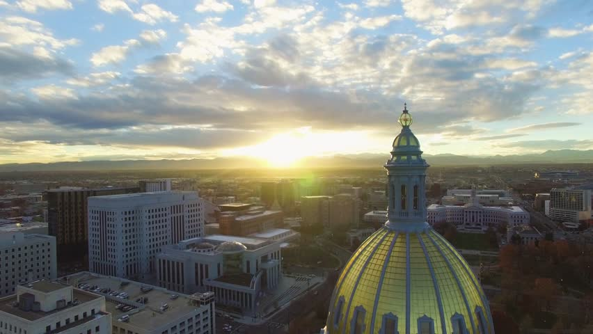 4k aerial/drone footage of the golden Colorado capital building in Denver at sunset.  The Rocky Mountains can be seen on the horizon