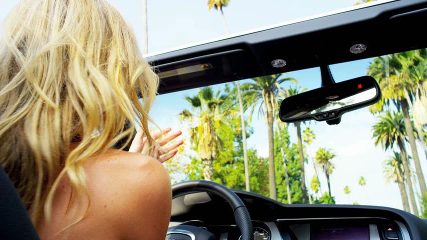 Blonde girl tossing hair open top car