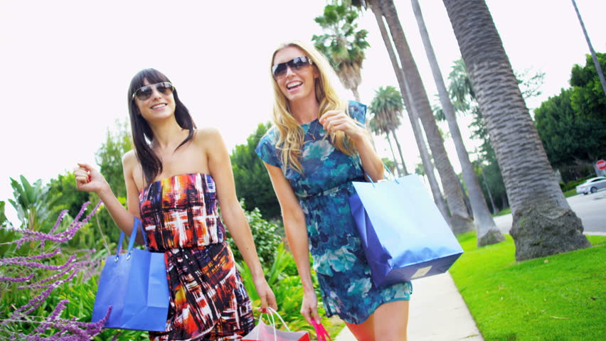 Two young girlfriends at their luxury car after a successful shopping trip | Shutterstock HD Video #2153267