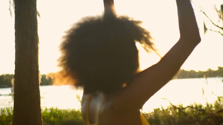 Young African American female park dancing freedom relax fun Summer holiday outdoors sun flare | Shutterstock HD Video #21535117