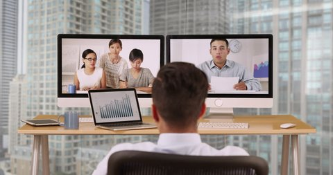 Businessman in highrise office talking to colleagues over video conference. Hispanic and Asian group of ethnically diverse group of business professional using computer for VoIP