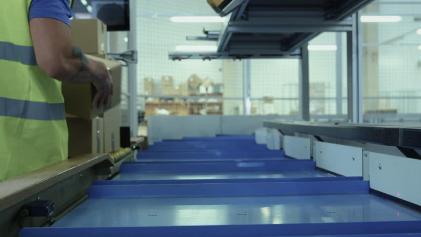Parcels are Moving on Belt Conveyor at Post Sorting Office. Box POV. Shot on RED Cinema Camera in 4K (UHD)