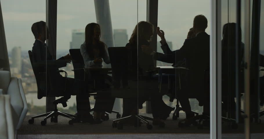 4k, Group of businesspeople high five together while standing in a modern boardroom. Slow motion.