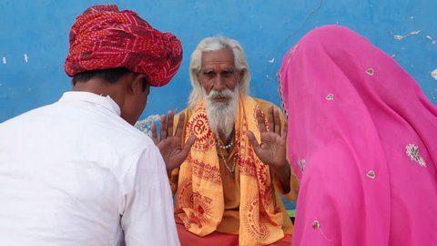 Bride in pink sari and Groom in white kurta and red turban seek blessing from an old Hindu Sadhu in safforn