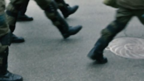 Security forces with dogs walking on the street. Legs close up