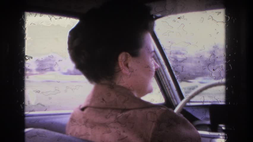 HOBOKEN NEW JERSEY 1966: a white woman with dark brown hair in a brown suede jacket operates a car in a suburban area