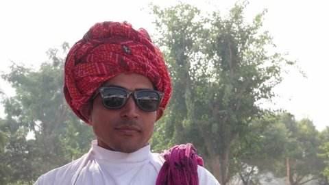 Dapper cool attractive Indian man in traditional dress and red turban wear sunglasses