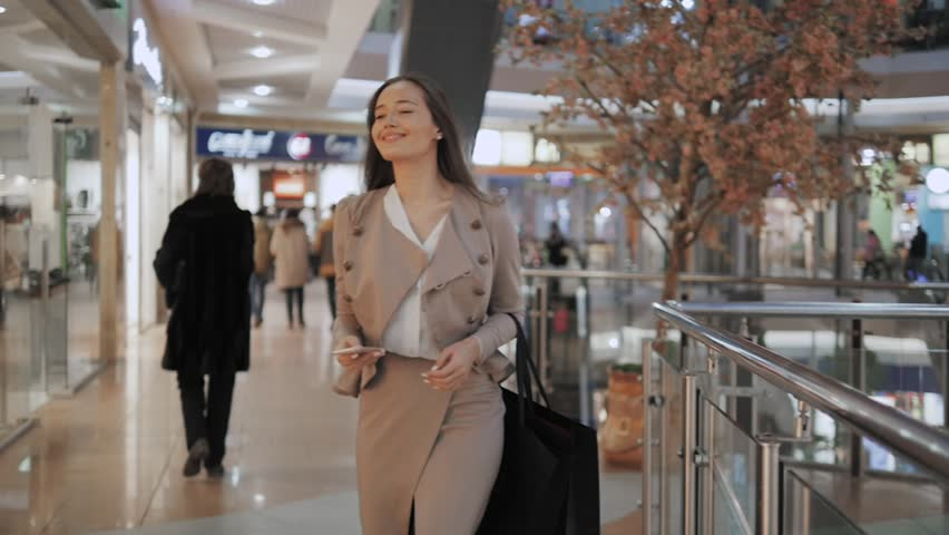 Shopping woman smiling with bags talking on the phone in mall. Beautiful girl with smartphone in shopping center. | Shutterstock HD Video #21655117