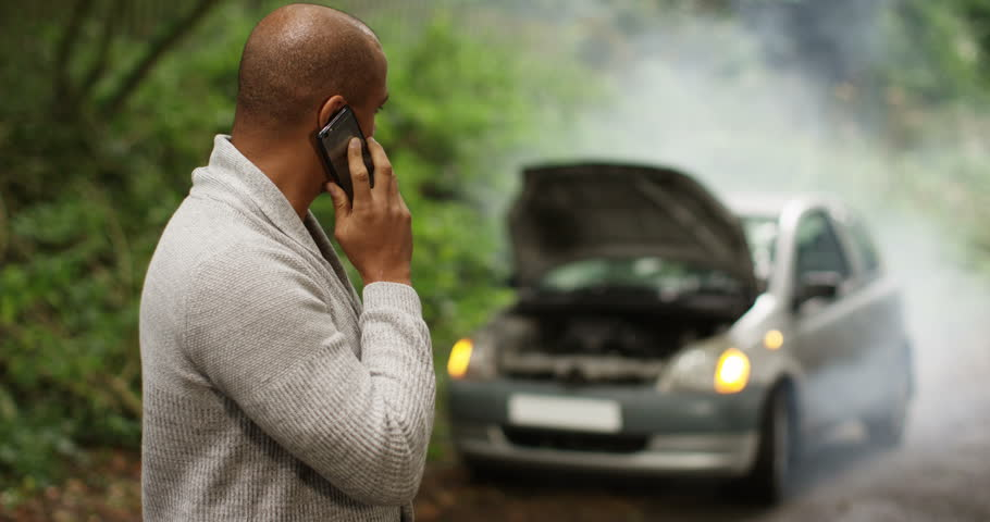 4k, Stranded young African American man talking on his cellphone with broken down car.