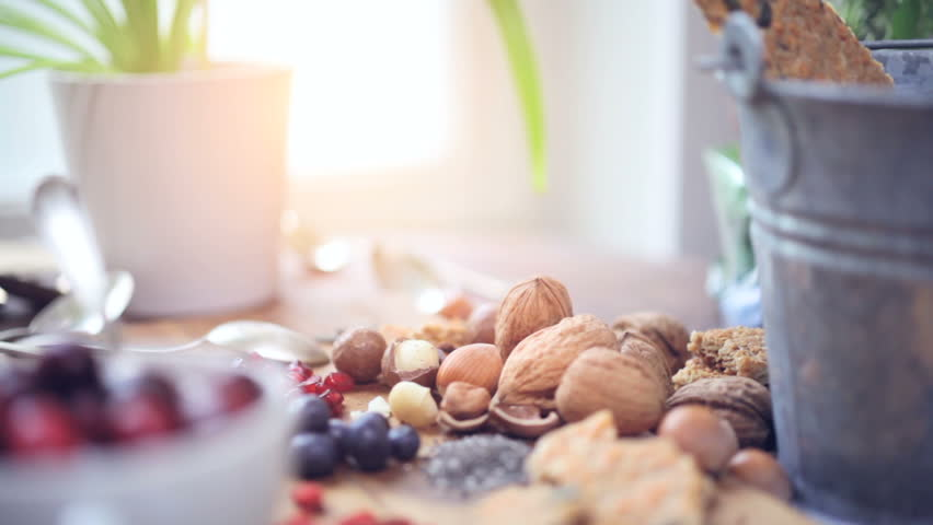 Superfood: variation of healthy superfoods ( berries, nuts and seed ) on wooden background, while sun is shining thru the window