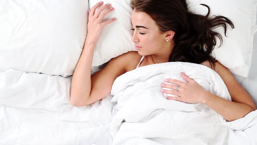 Attractive young woman waking up in bed at home