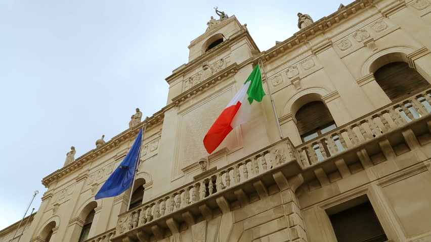 Italian and European flags on the historic building of Town Hall of Padua. Palazzo Moroni, Comune di Padova, shooting from the bottom of. Palazzo Moroni - seat of the Municipality of Padua, Italy