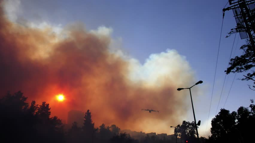Amphibian airplane drops fire retardant on a forest fire near gas station