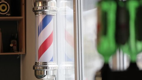 Barber Pole Spinning at a Barbershop. Shot from hands with shakes.